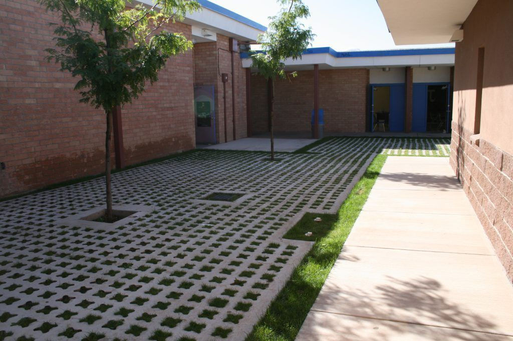 Partially concealed Bomanite Grasscrete was installed in this school courtyard to create a solution for stormwater runoff and add a beautiful visual aesthetic with the broom finished concrete and planting material.